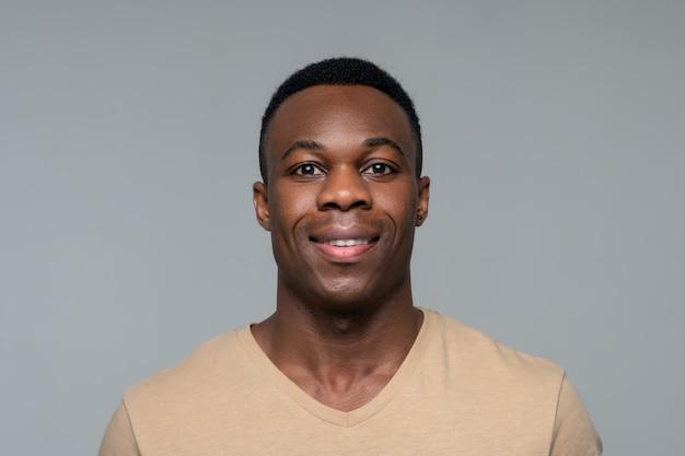 Großartige stimmung. lächelnder dunkelhäutiger junger erwachsener mann in hellem t-shirt, der gut gelaunt posiert