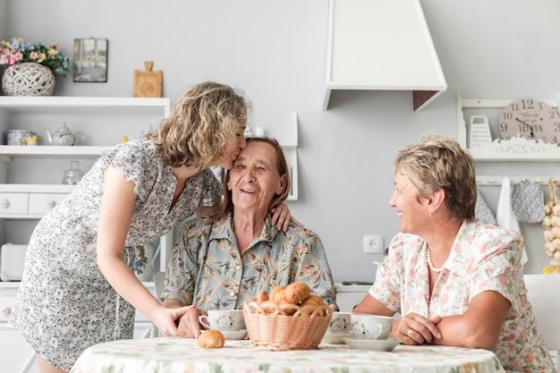 Großartige tochter, die ihre lächelnde oma während des frühstücks küsst