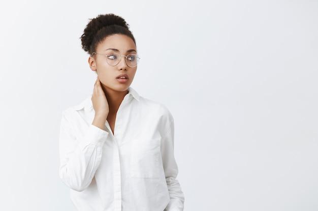 Großartiger chef lästig zu sein. stilvolle und zarte afroamerikanische büroangestellte in brille und weißem hemd, den hals berührend und mit verträumtem müden ausdruck rechts blickend, schmerz im nacken fühlend