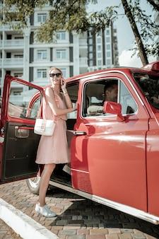 Großartiger redner. lächelnde hübsche frau, die an ihrem telefon spricht, das vor der autofahrt in das rote retro-auto einsteigt.