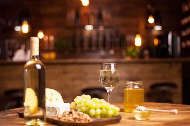 Großartiger weißwein auf einem rustikalen schreibtisch bei einer käseverkostung in einer vintage-kneipe. leckere trauben. flasche weißwein. frisches obst.