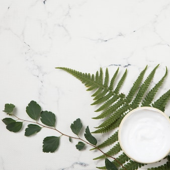 Großaufnahme der creme und der blätter auf marmorhintergrund