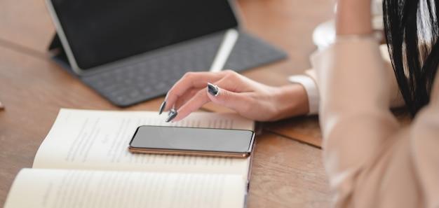 Großaufnahme der geschäftsfrau, die ihren smartphone beim arbeiten an ihrem projekt im bequemen arbeitsplatz verwendet