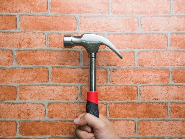 Großaufnahme der hand eines mannes, die hammer mit backsteinmauer hält. reparatur und wartung.