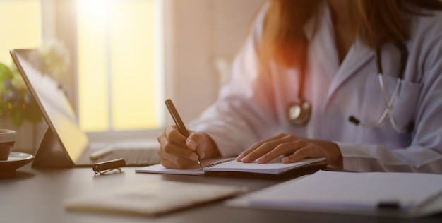 Großaufnahme der jungen ärztin medizinische diagramme mit tablette in büroraum schreibend