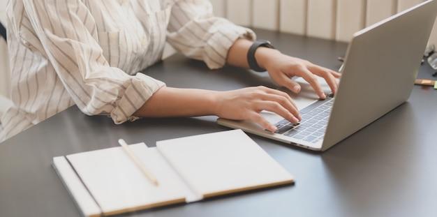 Großaufnahme der jungen schönen geschäftsfrau, die auf laptop-computer schreibt
