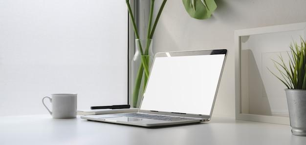 Großaufnahme des arbeitsplatzes mit laptop-computer und kaffeetasse des leeren bildschirms