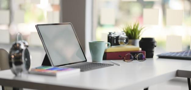 Großaufnahme des bequemen designerarbeitsplatzes mit tablette und büroartikel des leeren bildschirms