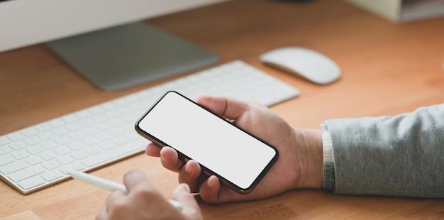 Großaufnahme des berufsgeschäftsmannes seinen smartphone des leeren bildschirms betrachtend