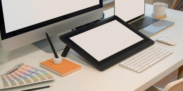 Großaufnahme des designerarbeitsplatzes mit digitaler tablette des leeren bildschirms mit tischrechner