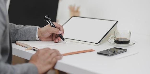 Großaufnahme des geschäftsmannes seine idee auf notizbuch in sein modernes büro schreibend