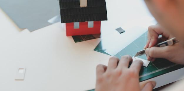 Großaufnahme des jungen männlichen architekten, der modell des kleinen hauses beim schnitt der pappe macht