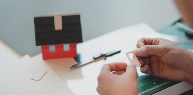 Großaufnahme des jungen männlichen architekten, der modell des kleinen hauses macht