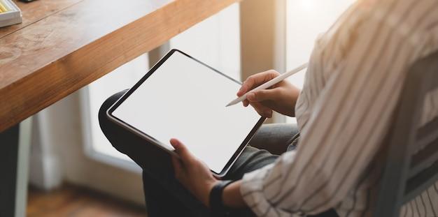 Großaufnahme des jungen weiblichen designers, der an tablette des leeren bildschirms arbeitet
