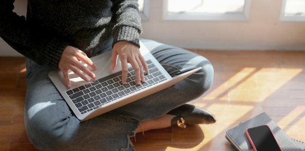 Großaufnahme des jungen weiblichen freiberuflers, der an ihrem projekt mit laptop-computer arbeitet