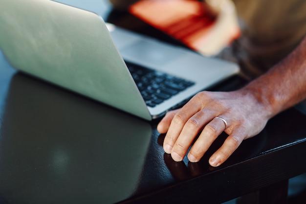 Großaufnahme des laptops und der männlichen hand mit dem ring