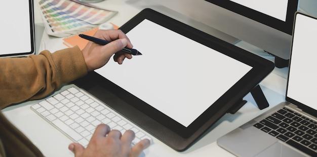 Großaufnahme des männlichen designers sein projekt auf digitaler tablette des leeren bildschirms bearbeitend