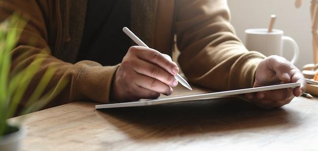 Großaufnahme des mannes arbeitend an seinem projekt bei der anwendung der tablette in seinem bequemen büro