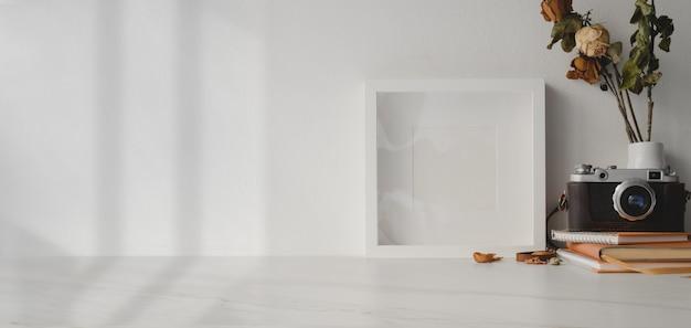 Großaufnahme des minimalen arbeitsplatzes mit modell herauf rahmen- und weinlesekamera auf weißem holztisch