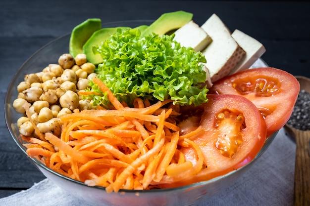 Großaufnahme von buddha-schüssel auf einer rustikalen tabelle. vegane mahlzeit aus kichererbsen, salat, gemüse, tofu und avocado