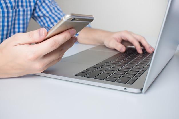 Großaufnahme von den geschäftsmännern, die unter verwendung der handys und des laptops auf einem weißen schreibtisch tragen.