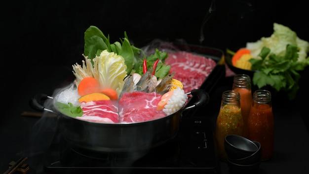 Großaufnahme von shabu shabu im heißen topf mit schwarzem hintergrund, frischem geschnittenem fleisch, meeresfrüchten und gemüse