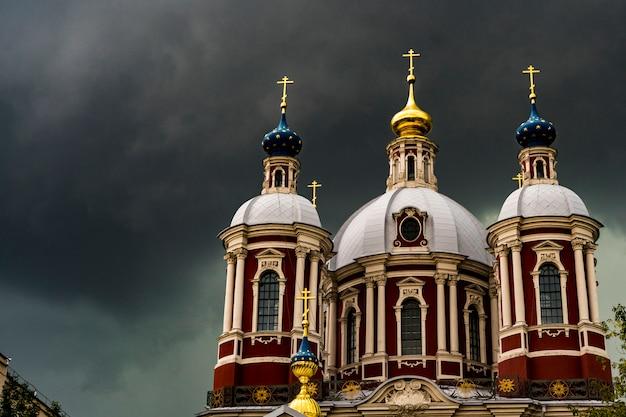 Große alte kirche gegen den dunklen bewölkten himmel während des strengen sturms