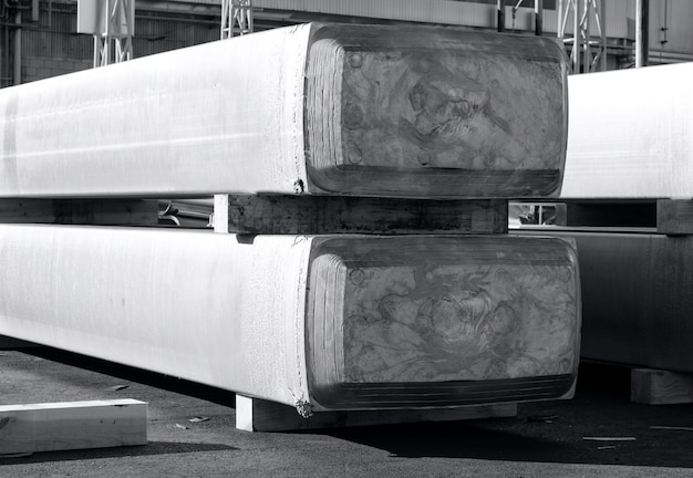 Große aluminiumbarren gestapelt in einer gießerei, rohstoff für die verarbeitung in einer heißen mühle. foto in schwarzweiß mit bläulichem ton