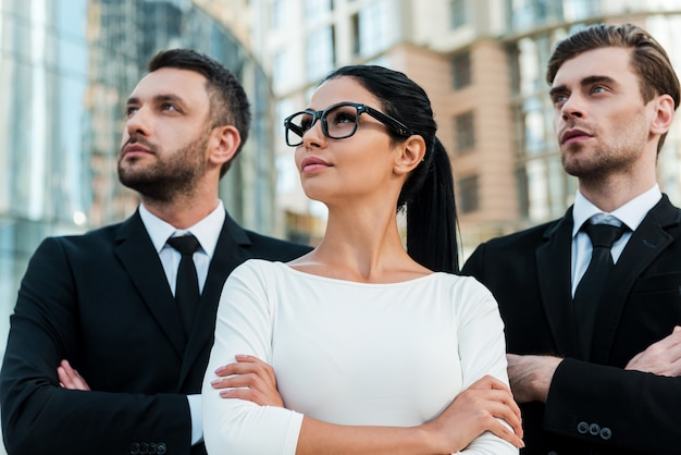 Große ambitionen eröffnen neue horizonte. low angle view von drei selbstbewussten geschäftsleuten