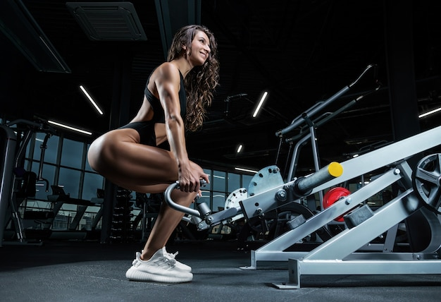 Große athletische frau hockt in der turnhalle in einem speziellen apparat