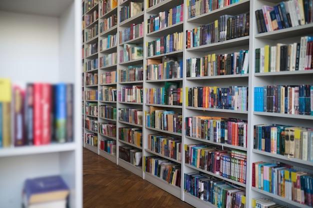 Große auswahl an belletristik und sachbüchern mit schönen bunten einbänden, die auf den weißen bücherregalen der bibliothek aus holz angeordnet sind