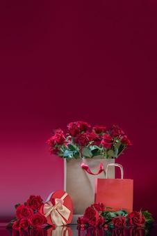 Große basteltasche gefüllt mit rosen herzförmige geschenkbox rosenperlen auf spiegelfläche