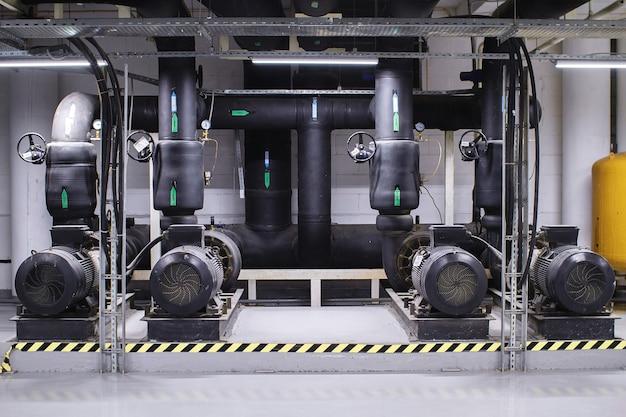 Große brauchwasseraufbereitung und heizungsraum. schwarze rohre, pumpen und ventile