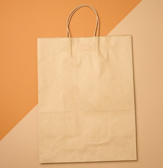 Große braune einweg-kraftpapiertüte mit griffen auf braunem hintergrund, öko-verpackung, kein abfall