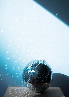 Große discokugel auf stuhl mit partylichtern