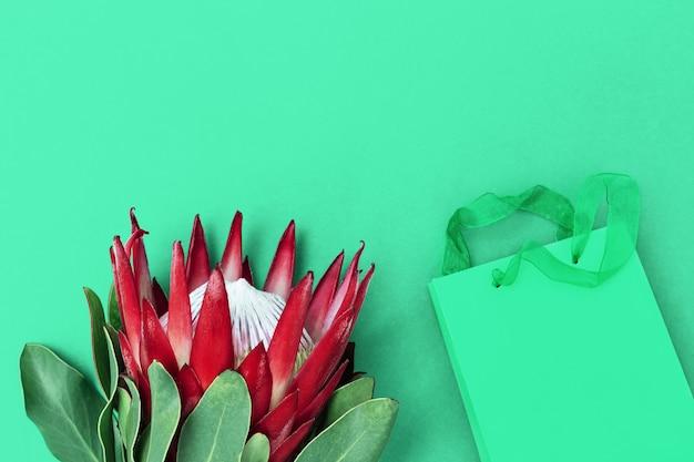 Große exotische blumenprotea mit roten blütenblättern und geschenk in papierverpackung