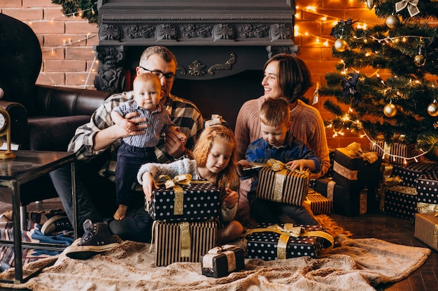 Große familie am heiligabend mit geschenken durch weihnachtsbaum