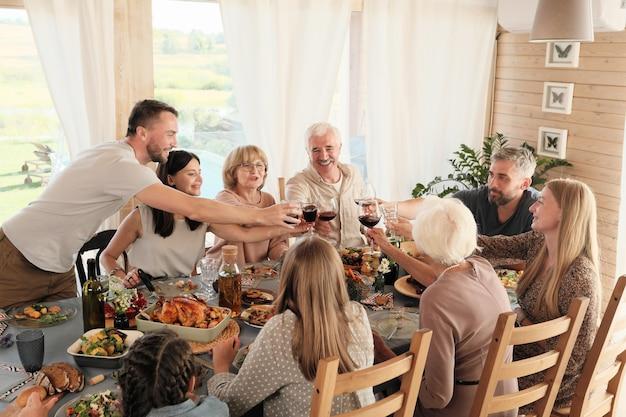 Große familie, die am tisch sitzt und mit gläsern rotwein anstößt, feiert feiertag zum abendessen