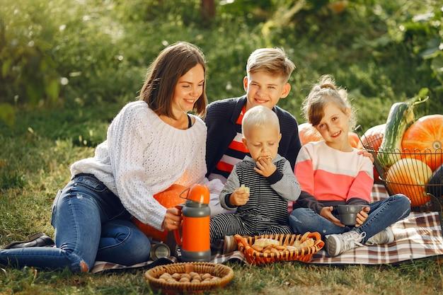 Große familie, die auf einem garten nahe vielen kürbisen sitzt