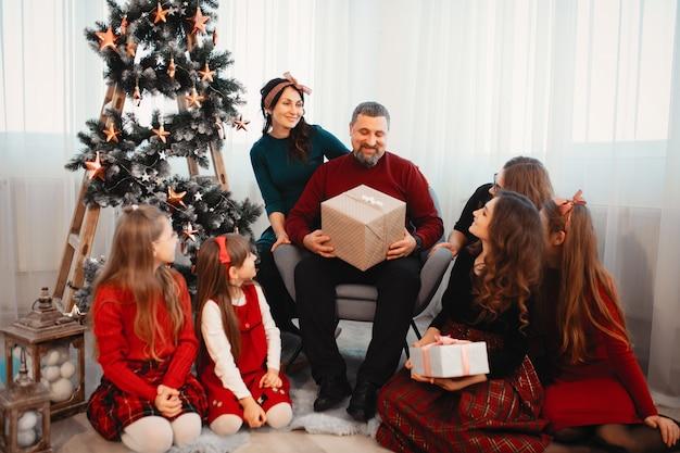Große familie, die zu hause nahe weihnachtsbaum sitzt