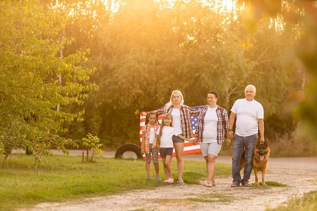 Große familie geht spazieren gehen amerikanische flaggen. vorderansicht, amerikanische patrioten auf der parkwiese.
