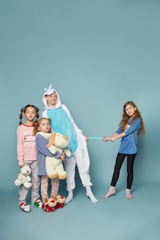 Große familie, kinder haben spaß und spielen morgens auf einem blauen. jungen und mädchen im nachtpyjama, eine freundliche große familie zusammen. ,