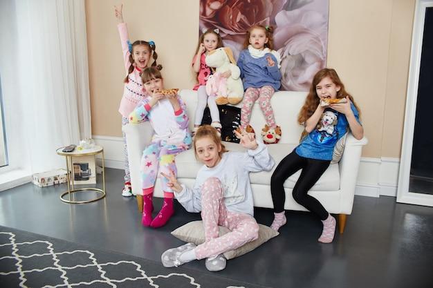 Große familie, kinder haben spaß und spielen morgens zu hause. jungen und mädchen im nachtpyjama
