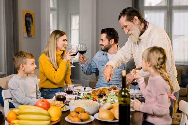Große familie mit kindern, die zusammen zu hause ein köstliches thanksgiving-abendessen haben