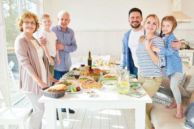 Große familie posiert am esstisch