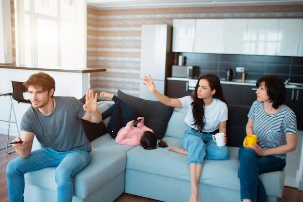 Große familie sitzt auf dem sofa. eine frau oder schwester spricht mit mutter und ruft ehemänner oder bruder an.