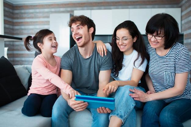 Große familie zu hause. alle zusammen kommunizieren online-konferenzen auf dem tablet. oder spielen sie ein lustiges handyspiel