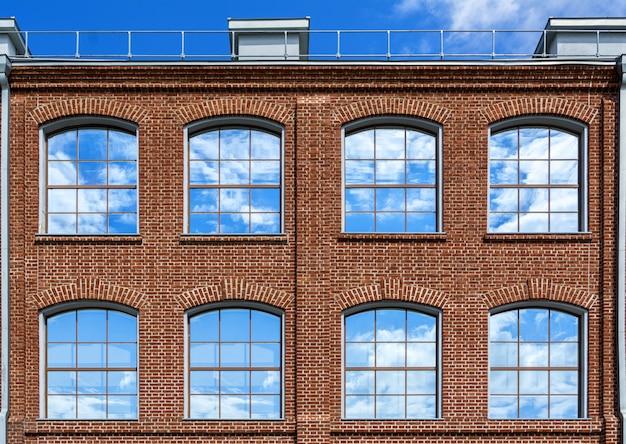 Große fenster mit einem spiegelbild des himmels. haus im loft-stil.