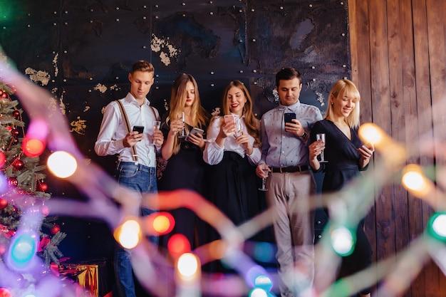 Große firma feiert ein neues jahr mit gläsern champagner mit handy-manie