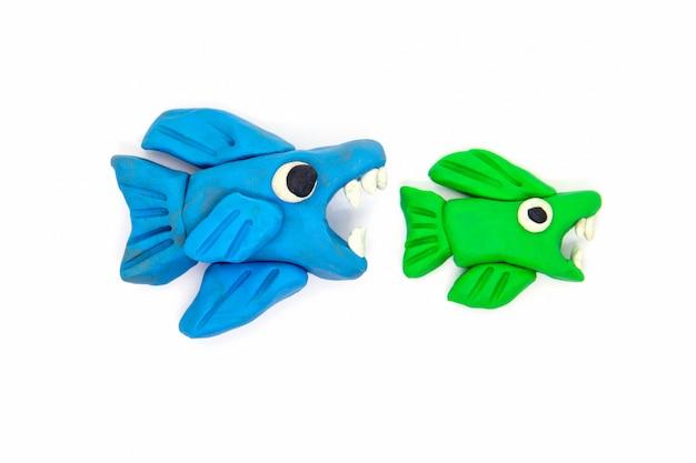 Große fische des spielteigs essen kleine fische auf weiß